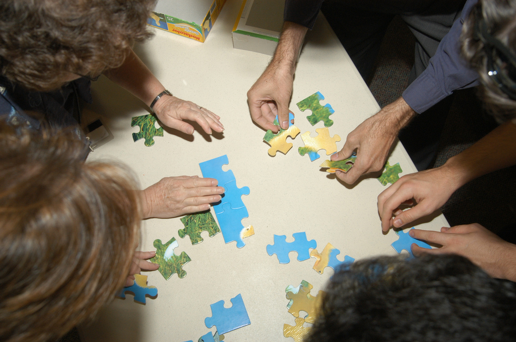 hands working on a jigsaw puzzle